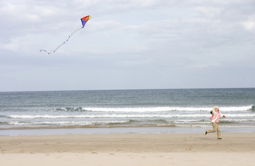 Girl (7-9) flying kite on beach