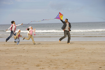 Family of four with kite on beach