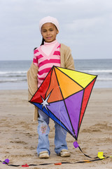 Girl (5-7) with kite on beach, portrait