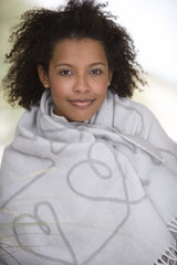 Woman wrapped in blanket, smiling, portrait