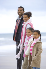 Family of four in row on beach, smiling, portrait