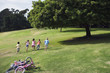 Group of children (7-9) running up grassy hill in park, leaving bicycles behind