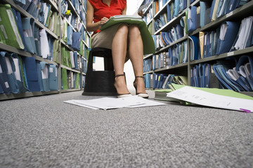 Woman wearing skirt and high heels, sitting on footstool in aisle of office archive, looking at file in lap, documents on floor, low section, surface level