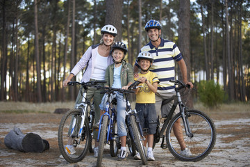 Two generation family standing beside bicycles in woodland clearing, smiling, portrait
