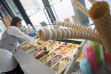 Man serving in ice cream parlour, smiling, side view, focus on background (tilt)