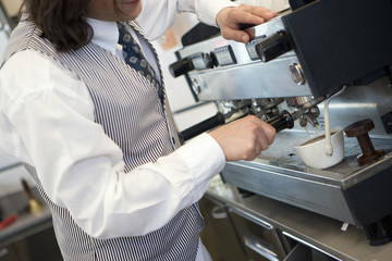 Waiter preparing beverage using expresso maker, side view, close-up, mid-section (tilt)