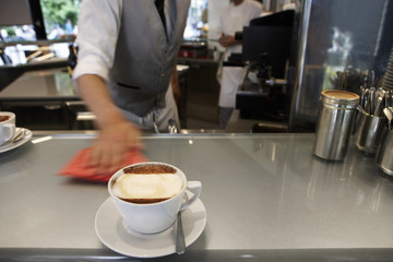 Waiter cleaning work surface in cafe, focus on beverage in foreground (blurred motion)