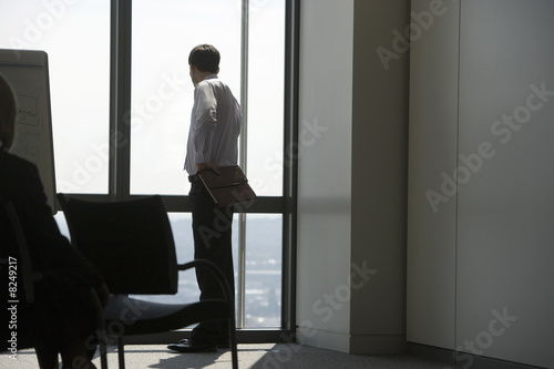 Businessman looking through window in conference room, waiting to begin presentation, rear view