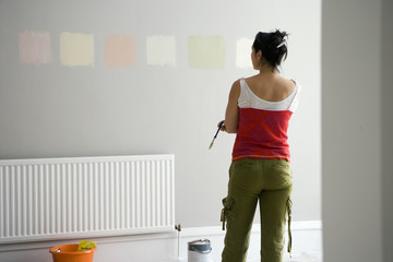 Woman looking at various paint colours on wall in undecorated room, making decision, rear view