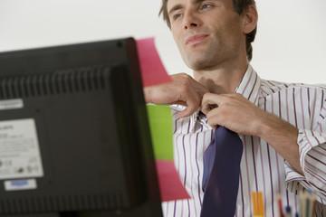 Businessman sitting at desk, adjusting tie, close-up (differential focus)