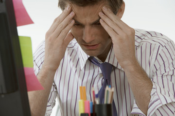 Stressed businessman sitting at desk, rubbing forehead, close-up (differential focus)