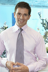 Businessman standing in office, smiling, front view, portrait, fish tank in background
