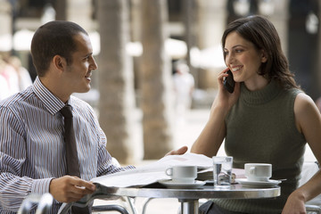 Couple sitting at pavement cafe table, businessman with newspaper, woman using mobile phone, smiling