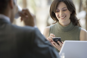 Couple sitting at pavement cafe table, focus on woman using personal electronic organiser, smiling