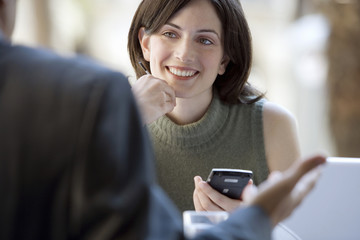 Couple sitting at pavement cafe table, focus on woman with personal electronic organiser, smiling