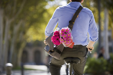 Man cycling, carrying shoulder bag and bouquet of pink flowers, close-up, rear view, mid-section
