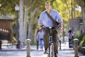 Spain, Barcelona, man cycling in city street, carrying shoulder bag, smiling, front view
