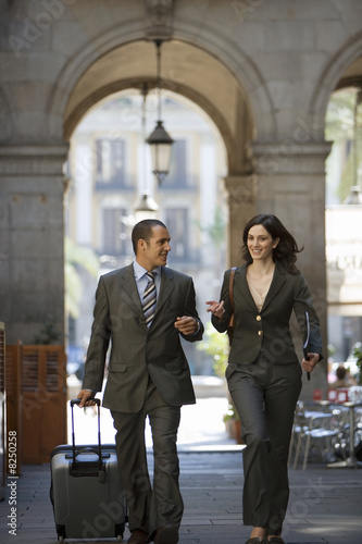 Spain, Barcelona, businessman and woman walking with luggage, smiling, archway in background
