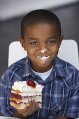 Boy (7-9) eating slice of cream cake, whipped cream on lips and nose, smiling, close-up, portrait