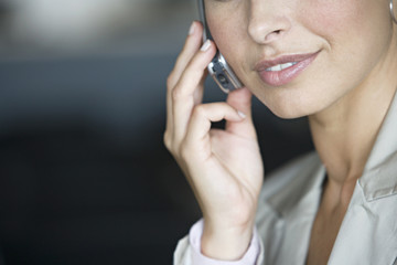 Businesswoman using mobile phone, close-up, mid-section, portrait