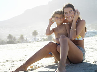 South Africa, Cape Town, mother and son (5-7) sitting on beach, listening to sea shells, smiling