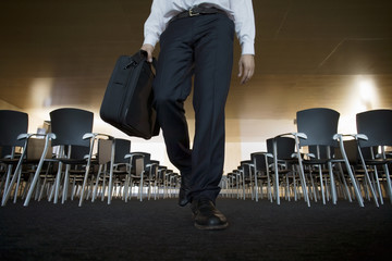 Businessman leaving empty conference room, carrying briefcase, low section, surface level