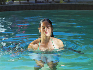 Teenage girl (15-17) relaxing in swimming pool, eyes closed, front view