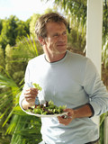 Man eating fresh salad on veranda, smiling