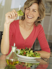 Woman eating fresh salad in kitchen, smiling, portrait