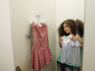 Teenage girl (15-17) trying on new clothes in fitting room, looking at reflection in mirror, smiling