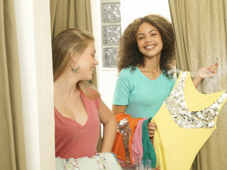 Teenage girls (15-17) trying on new clothes in fitting room, girl with yellow top, smiling, portrait