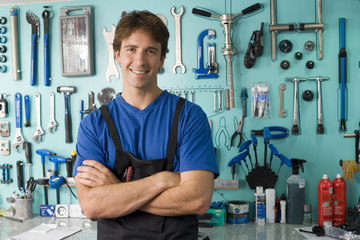 Man standing in front of display rack in tool shop, arms folded, smiling, front view, portrait