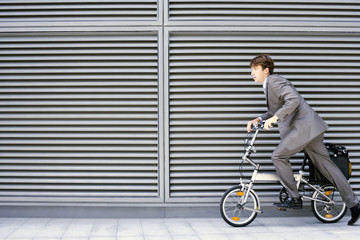 Businessman cycling on folding commuter bicycle on pavement, profile