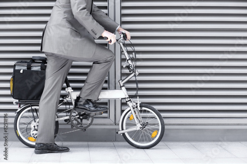 Businessman cycling on folding commuter bicycle on pavement, side view, low section