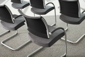 Row of chairs in conference room, close-up, rear view