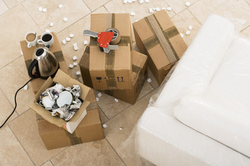 Duct tape, boxes, crockery, kettle and cups beside sofa wrapped in plastic sheet, overhead view