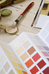 Small paint tins, paintbrush, DIY magazine and colour swatches on floor, close-up (still life)