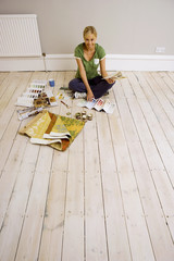 Woman decorating at home, sitting on floor in sparse room, holding colour swatch, smiling, portrait