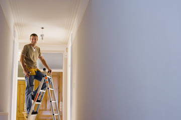 Man with toolbelt doing DIY at home, standing on step ladder below ceiling light fixture, portrait