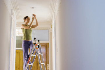 Woman doing DIY at home, standing on step ladder, attaching light bulb to ceiling fixture, smiling