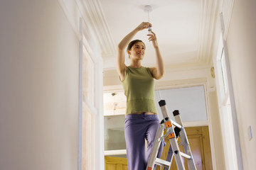 Woman doing DIY at home, standing on ladder, attaching light bulb to ceiling fixture, low angle view