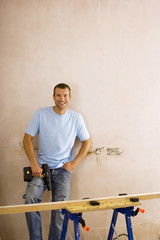 Man doing DIY at home, standing beside timber on workbench, holding power drill, smiling, portrait