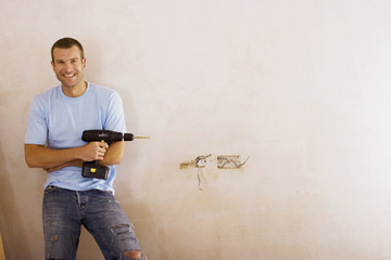Man doing DIY at home, holding power drill, smiling, front view, portrait