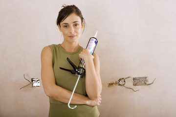 Woman doing DIY at home, holding glue gun, smiling, front view, portrait