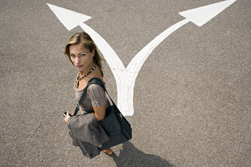 Businesswoman standing in car park near opposing arrow signs, side view, portrait, elevated view