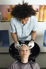 Young male hairdresser shampooing woman's hair in salon, front view, elevated view