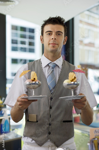 Waiter serving ice cream desserts in cafe, smiling, front view, portrait