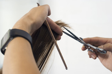 Hairdresser cutting woman's hair in salon, close-up of comb and scissors (personal perspective)