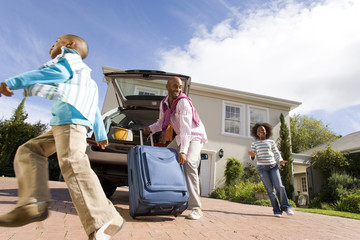 Two children (8-10) running by father packing suitcase into boot of car, smiling, low angle view