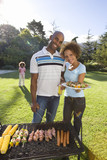 Couple standing by barbeque outdoors, holding plate of food, smiling, portrait